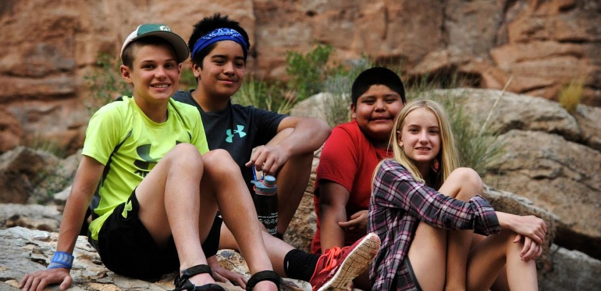 Four Grand Canyon Youth sitting on a rock during a group expedition