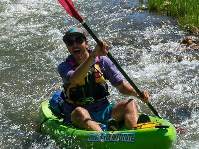 Grand Canyon Youth Field staff director Jean-Philippe rowing a green hard shell kayak