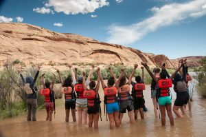 Healing Lands Project Youth standing in water with arms up