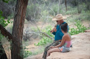 Grand Canyon Youth river guide playing flute with a child on Healing Lands River Trip