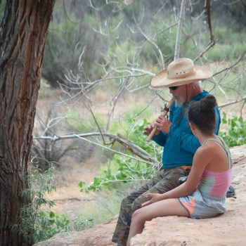 Grand Canyon Youth river guide playing flute with a child