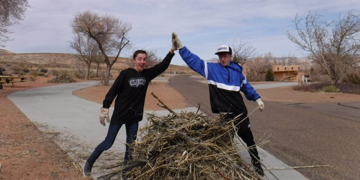 Two Grand Canyon Youth alumni high fiver over a pile of brush Service project pandemic pickup