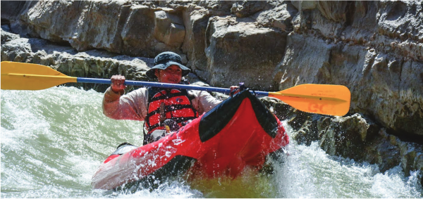 Grand Canyon Youth Alumna rowing a red inflatable kayak on the San Juan River