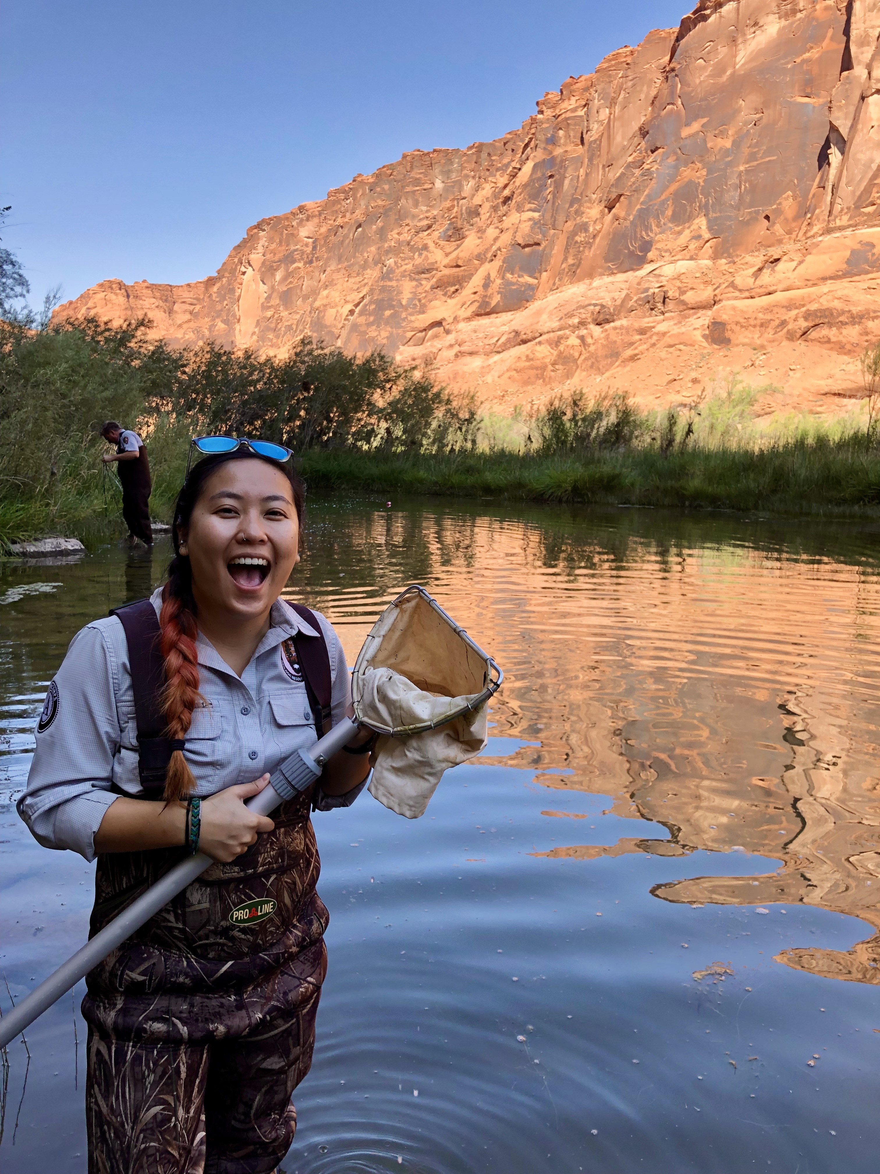 A scienctist stands in knee deep water in a red rock canyon holding a net and a big smile on her face with a