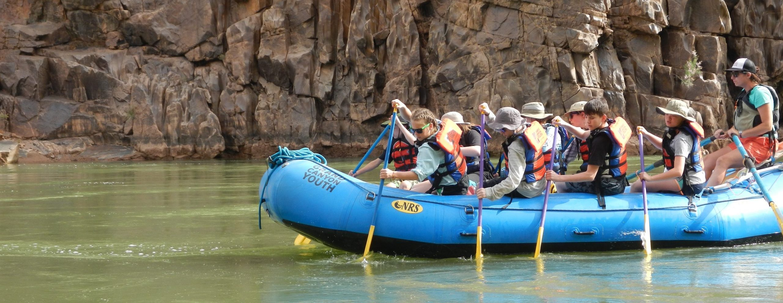 Grand Canyon Youth alumni rowing a blue paddle boat with a guide on the back